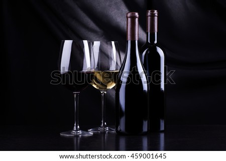 Two bottles and glasses of red and white wine over a dark background