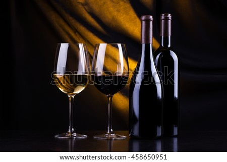 Two bottles and glasses of red and white wine over a dark yellow lit background