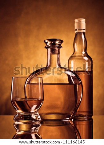 Two bottles of alcohol and a glass on brown grunge background - stock photo