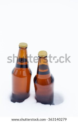 Two bottles of beer chilling in snow - stock photo