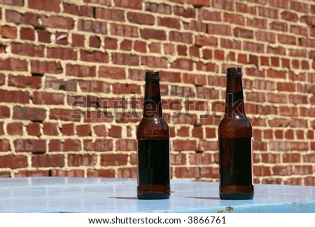 Two bottles of beer on a table at an urban pub's outdoor patio. - stock photo