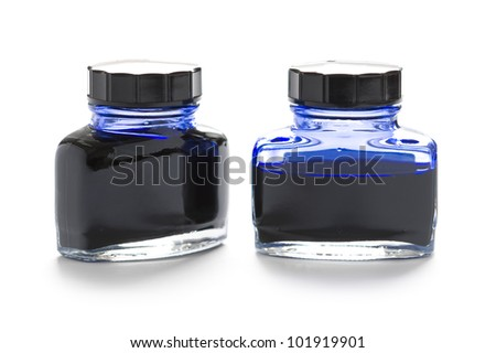 two bottles of blue writing ink one half empty