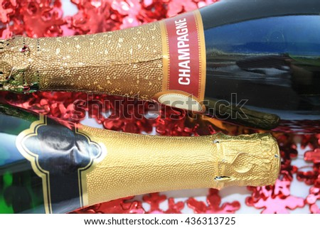 Two bottles of champagne on a christmas decorations background - stock photo
