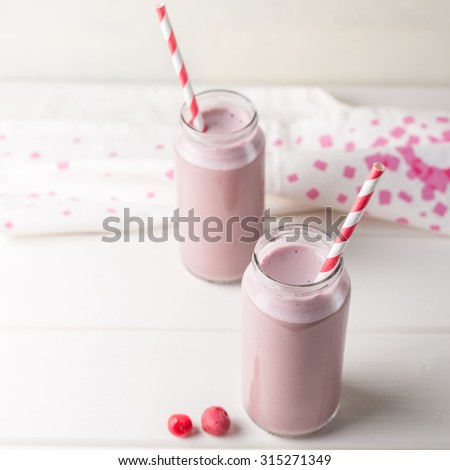 Two bottles of cherry smoothie isolated on white background - stock photo