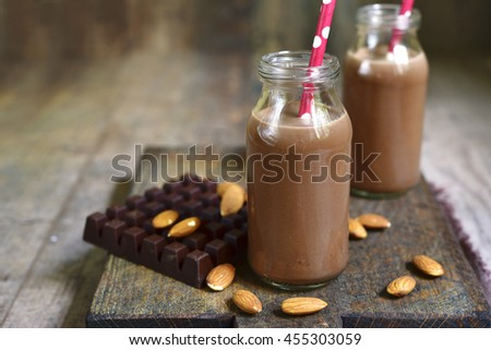 Two bottles of chocolate almond milk with paper straws on a rustic wooden background.