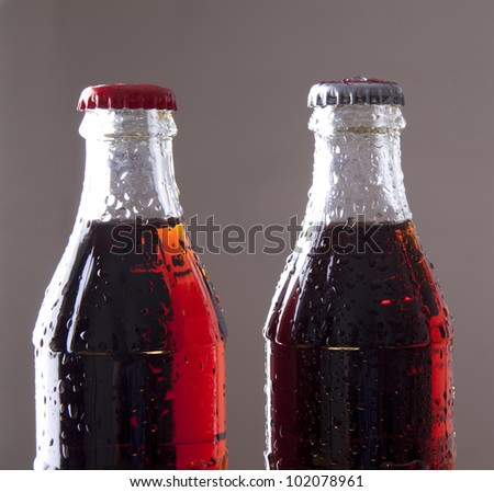 two bottles of cold cola with water drops. Isolated on gray background - stock photo