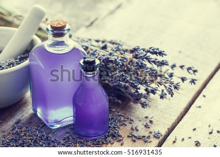Two bottles of essential oil, mortar and lavender flowers bunch on table. Retro toned photo. Selective focus.