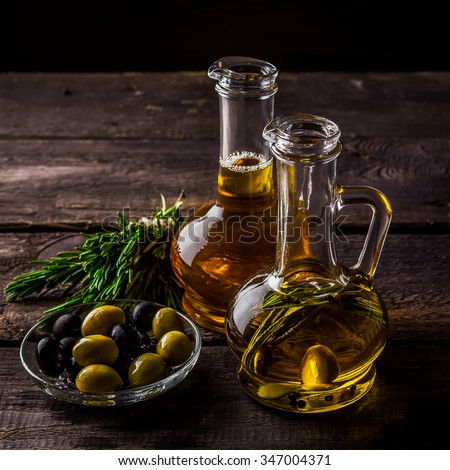 Two  bottles of olive oil, olive in a bowl and herbs on a wooden table. Selective focus. - stock photo