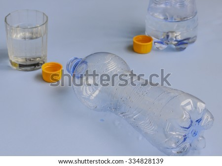 two bottles of water drained ,with orange cap and the glass - stock photo