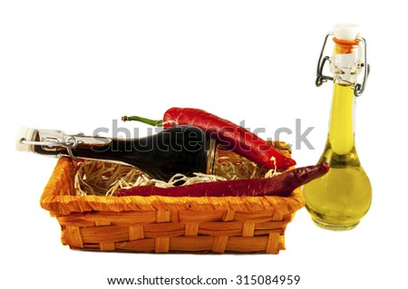 Two bottles of wine vinegar, olive oiland two red hot chilly peppers  in a gift box isolated on white background - stock photo