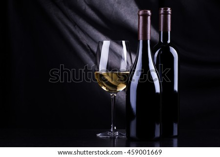 Two bottles of wine with a glass of white wine over a dark background