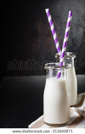 Two bottles with milk on dark background with purple striped straws