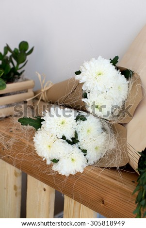 Two bouquets of white chrysanthemums in a paper cornet