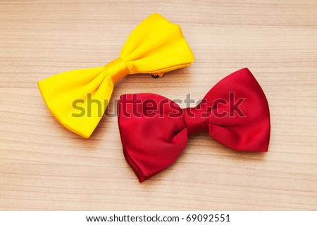 Two bow ties on the wooden background - stock photo