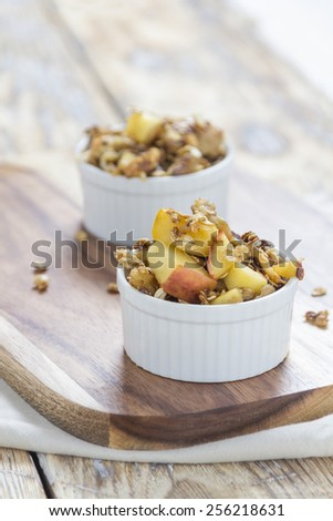 Two bowls of Apple Crumble on a wooden board on a rustic Table  - stock photo