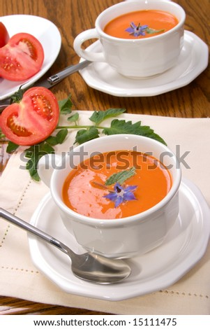 Two bowls of delicious tomato soup garnished with borage flower and leaves