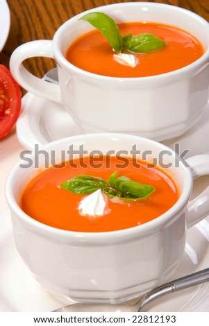 Two bowls of delicious tomato soup garnished with cream and basil leaves - stock photo
