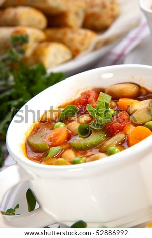 Two bowls of hot fresh Minestrone soup and cheese garlic breadsticks - stock photo