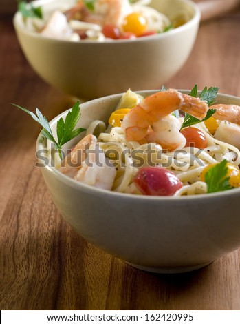 Two bowls of linguine pasta with shrimp and vegetables.