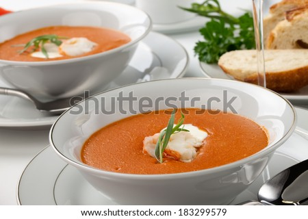 Two bowls of lobster bisque garnished with slice of lobster tail, cream, and fresh tarragon. Fresh backed Italian bread and white wine.