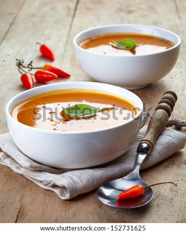 two bowls of squash soup on a wooden table - stock photo