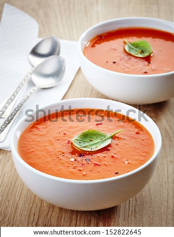 two bowls of tomato soup on wooden table - stock photo