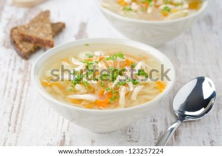 two bowls vegetable soup with chicken and parsley horizontal