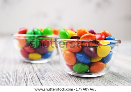 Two bowls with multicolor candies on a desaturated background - stock photo