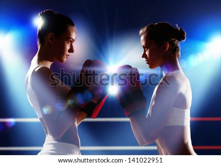 Two boxer women in gloves greet each other before fight - stock photo