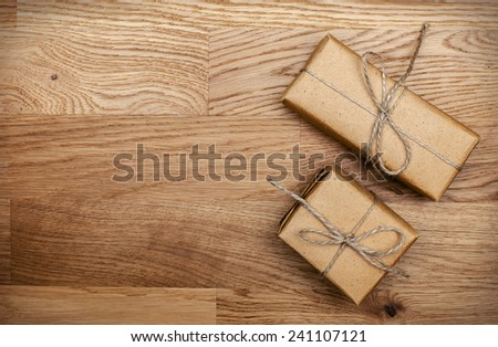Two boxes in eco paper on the wooden table. Top view. Parcels or gifts tied with twine. - stock photo