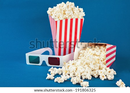 Two boxes of popcorn and 3D glasses on blue background - stock photo