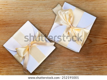 Two boxes with golden ribbon on wool - stock photo