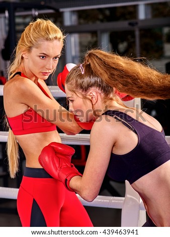 Two boxing women wearing red boxing gloves are boxing on boxing ring. - stock photo