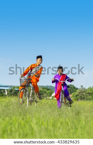 two boy cycling on paddy field during blue sky - stock photo