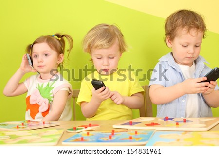 Two boys and a girl with phones in their hands are sitting at a table with toys