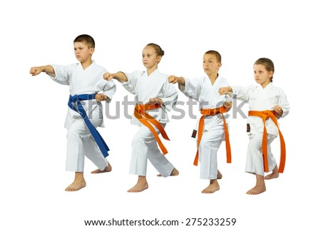 Two boys and two girls in karate position make punch - stock photo
