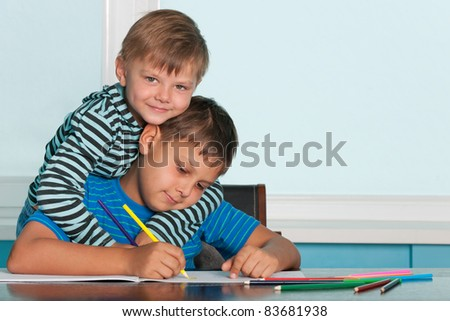 Two boys are sitting at the desk and drawing - stock photo