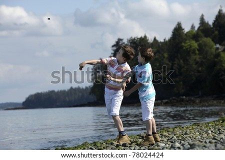 two boys at a beach throwing rocks
