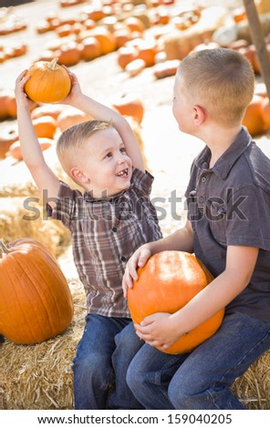 Two Boys at the Pumpkin Patch Talking About Their Pumpkins and Having Fun on a Fall Day.