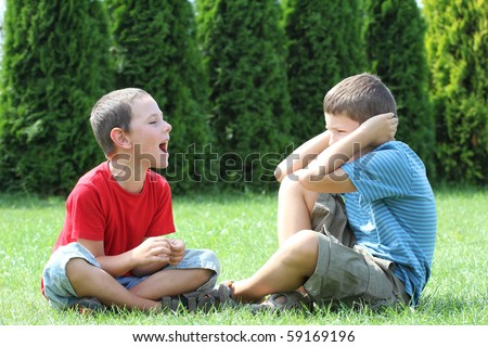 Two boys, brothers, sibling quarreling. - stock photo