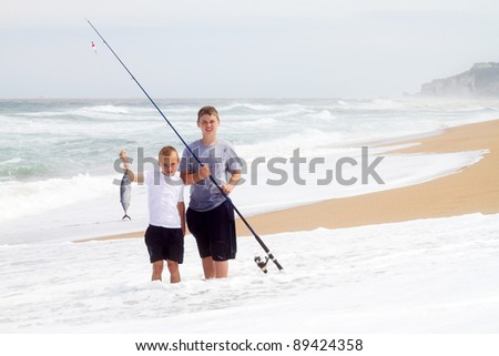 two boys catching a big fish on beach - stock photo
