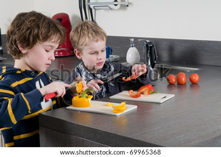 Two boys cutting some red and yellow peppers, used for cooking. - stock photo