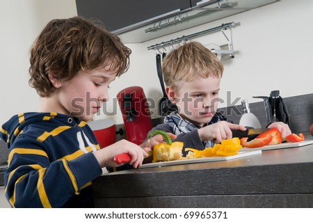 Two boys cutting some red and yellow peppers, used for cooking.