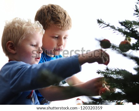 Two boys decorating the Christmas tree. - stock photo