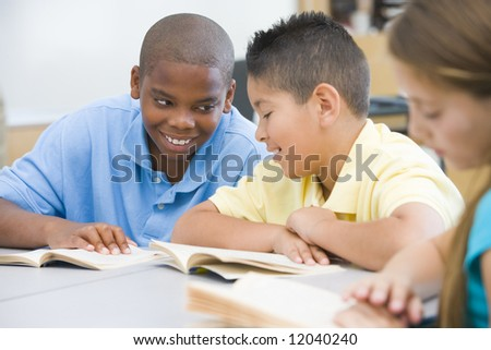 Two boys discussing book whilst seated at desk