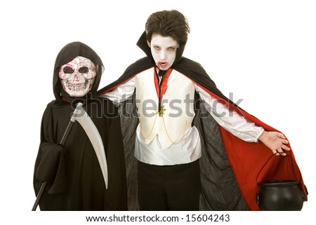 Two boys dressed for Halloween as a vampire and the grim reaper.  Isolated on white. - stock photo