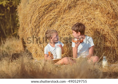 two boys drink milk in the village