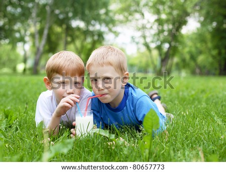 Two boys drinking milk in the summer outdoors