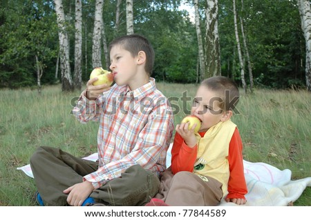 Two boys eat apples in the forest
