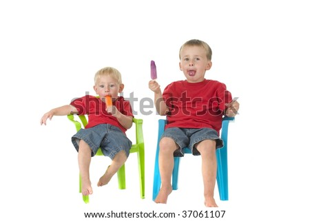 Two boys eat popsicles on lawn chairs - stock photo